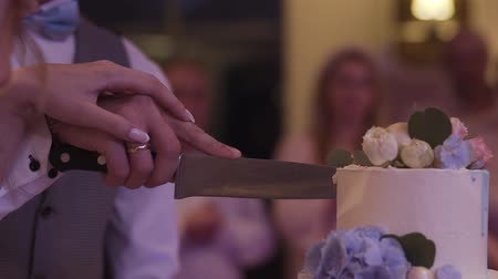 новобрачный : Happy newlyweds cut a wedding cake at a celebration.