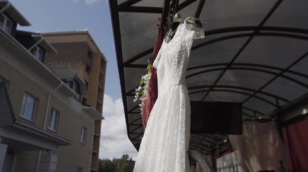 goes : Beautiful white wedding dress hanging on the street.