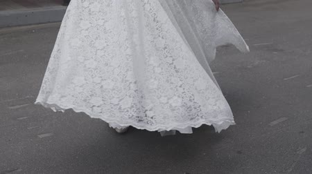 comes : Happy bride in a wedding dress on the street.