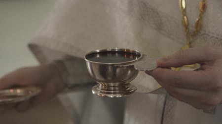 rahip : the priests hand baptizes a cup of wine.