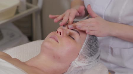 омоложение : Professional beautician woman doing facial massage to patient. Стоковые видеозаписи