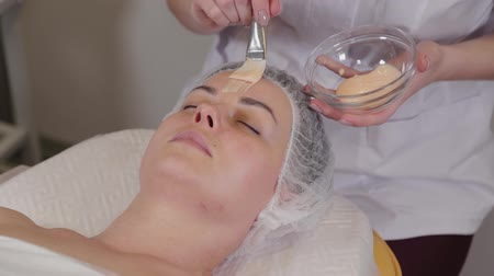 masaż twarzy : Professional cosmetologist woman puts a mask on the face of the patient. Wideo