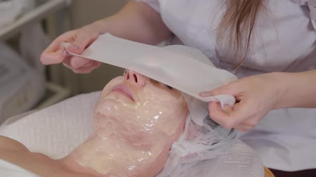 collagen : Professional beautician woman covers the mask with face bandages.