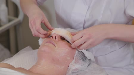 čelo : Professional cosmetologist woman removes bandages from the face of a client. Dostupné videozáznamy