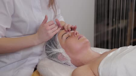 terapeuta : Professional cosmetologist woman doing facial massage to client of beauty salon.