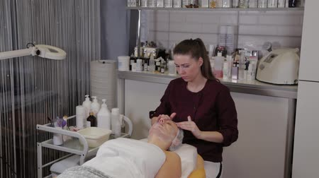 массаж : A professional beautician washes the patients face with liquid soap and simultaneously massages.