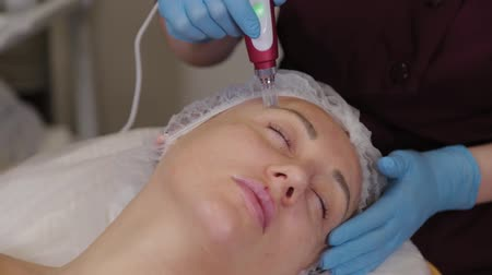 invasive : Professional beautician woman performs micronidling facial skin.