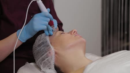 mezoterapia : Professional beautician woman performs micronidling facial skin.