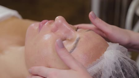 анти : Professional cosmetologist woman doing facial massage to client of beauty salon.