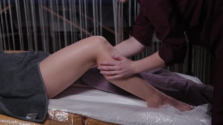 cellulite treatment : Professional beautician woman massages legs of a client in a beauty salon. Stock Footage