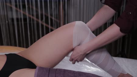 целлюлит : Professional beautician woman performs body wrap procedure in a beauty salon. Стоковые видеозаписи