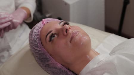 cosmetic surgery : Beautiful young woman in a cap at the beauty parlor. Stock Footage