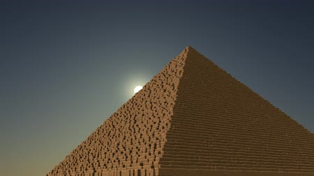 piramit : Slow camera move around two pyramids. Blue sky, low sun background