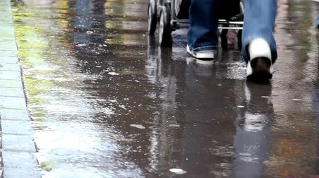 step : Pedestrians passing by on a wet sidewalk or pavement.