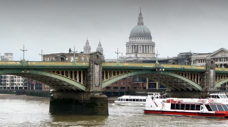 londra : Southwark bridge in central London.An overcast, rainy day. St Pauls in the background. Some boats going under the bridge. Stok Video