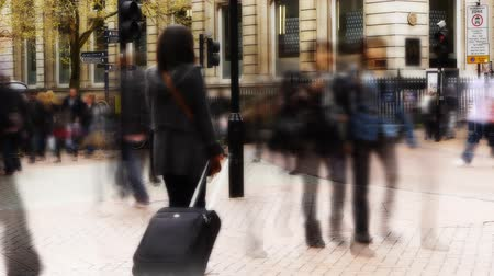 kufr : A woman with a suitcase stands still as blurred people move past her in a city environment.