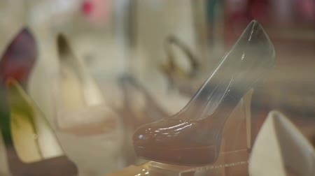 sapato : Part of a shop window shoe display. People walking past are reflected in the glass. The display is sharp. The people are blurred.