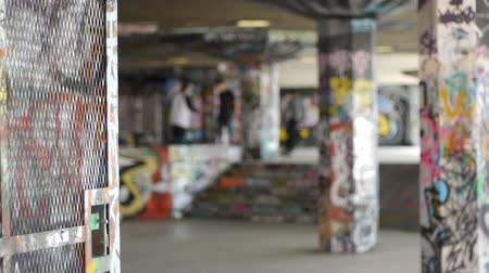 patim : A group of skateboarders in a colorful, graffiti covered space under a building.