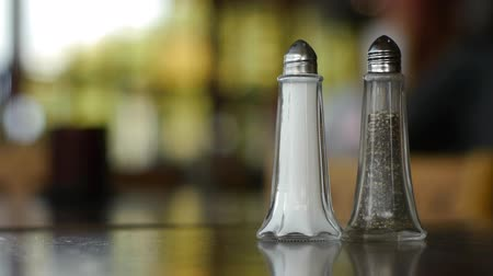 sůl : Salt and pepper shakers on a table in a dining room. background is blurred.