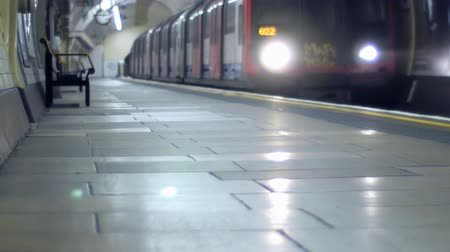 tüp : An underground train arrives at a platform and passengers get off.