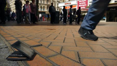 cüzdan : A lost wallet lies on the ground. Many people walking past. Stok Video