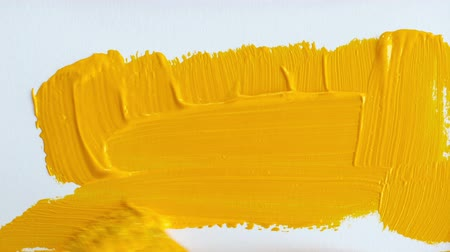 orange : A blank piece of paper is painted with thick orange paint by a brush. Stock Footage