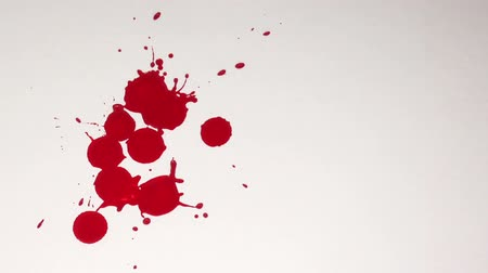 krew : Drops of blood fall and splatter onto a white paper background.