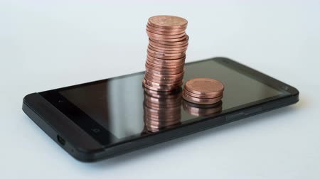 payment : Piles of pennies appear from the screen of a smart   phone.