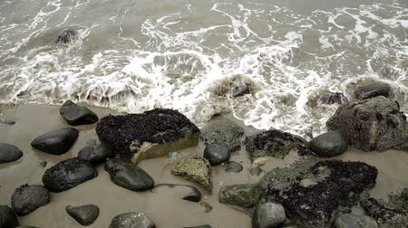 Small wave breaks over sand and rocks on a shoreline.