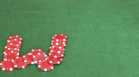 toco : On empty green table word win out of casino chips, red w leeter, black i and blue n, gambling, poker game. Stop motion. Close up, 4K Ultra HD.