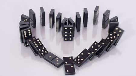 оставаться : A finger pushes black domino and it causes whole chain to fall in shape of heart but three stay up, domino effect, row of dominos falling. Close up, slow motion. Стоковые видеозаписи
