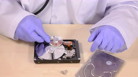 silme : Person in purple rubber gloves and white coat checks hard disk drive with stethoscope, top part and screws lay on table, concept of checking hdds wellbeing, data security. Close up, 4K Ultra HD. Stok Video
