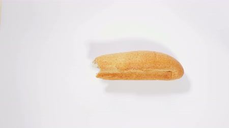 partially : Baguette disappears bite by bite on white background, eating bread, pastries, bakery, wheat bran, healthy food. Close up, stop motion, 4K Ultra HD.
