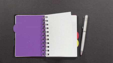 planos : Black dotty spiral notebook with colorful dividers, silver pen on black table, turning over clean white pages. Close up, stop motion, 4K Ultra HD.