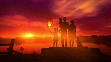 The family launches a Chinese lantern at sunset