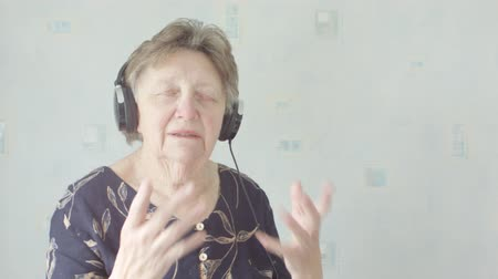 sobre : Active Senior caucasian woman listening and singing to music on MP3 player at home on headphones