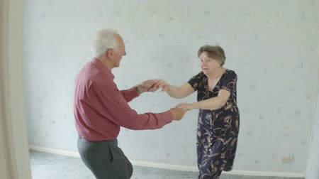 piada : Active young at heart Senior Caucasian couple jive dancing in their living room