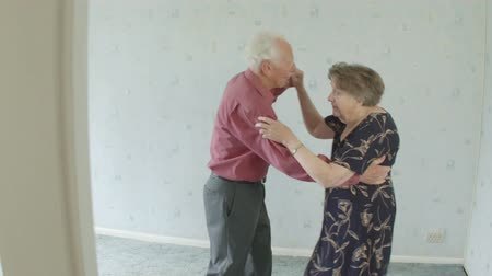 sobre : Active young at heart Senior Caucasian couple jive dancing in their living room