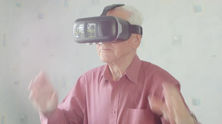 sobre : Active Senior Caucasian man wearing virtual reality headset in his home playing 360 video game
