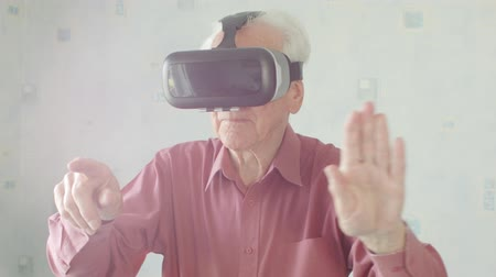 přenosný : Active Senior Caucasian man wearing virtual reality headset in his home playing 360 video game