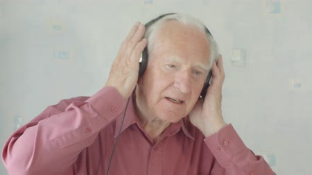 Active Senior caucasian man listening and singing to music on MP3 player at home on headphones
