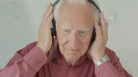 sobre : Active Senior caucasian man listening and singing to music on MP3 player at home on headphones