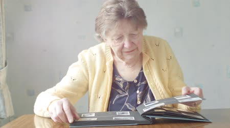 Senior Caucasian woman looking through old photograph album of photos of herself as a child