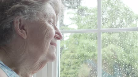 Retired Senior Caucasian woman looking out of her window with sadness and contemplation on a rainy day