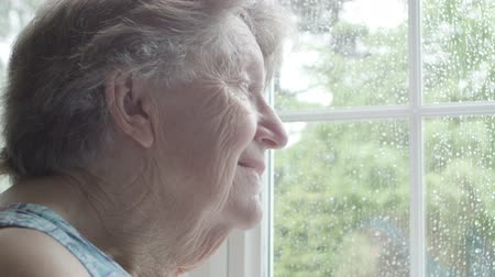 diferansiyel odak : Retired Senior Caucasian woman looking out of her window with sadness and contemplation on a rainy day
