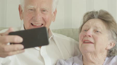 Happy Senior Caucasian couple taking selfies on a smartphone