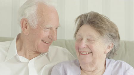 Portrait of a happy Senior couple looking at the camera in their living room