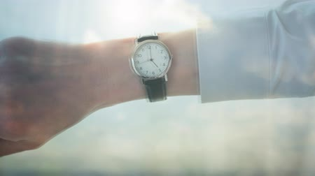 punctuality : Reflection of a caucasian businessman checking the time cityscape behind ready to leave the office themes of appointment urgency punctuation schedule Stock Footage