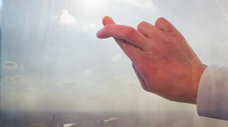 Businessman crossing his fingers against a window backlit by the sun