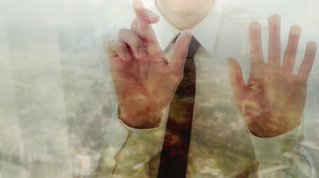 Reflection of a businessman crossing his fingers against a window with a cityscape behind